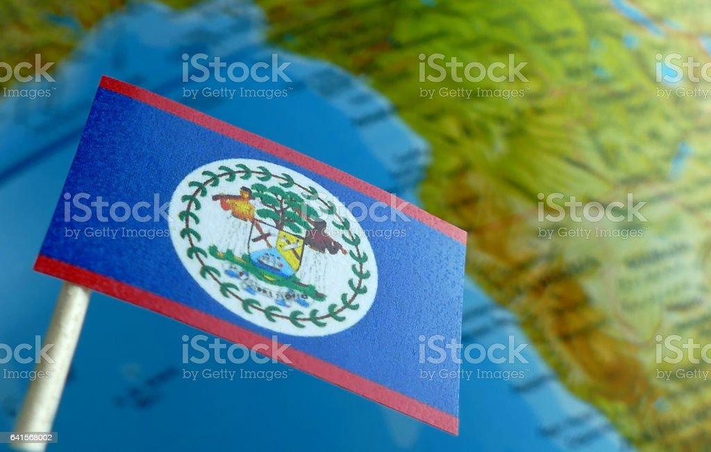 Belize flag with a globe map as a background macro stock photo