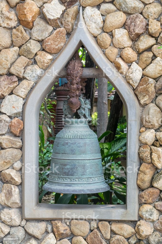 bell and rustic stone wall stock photo