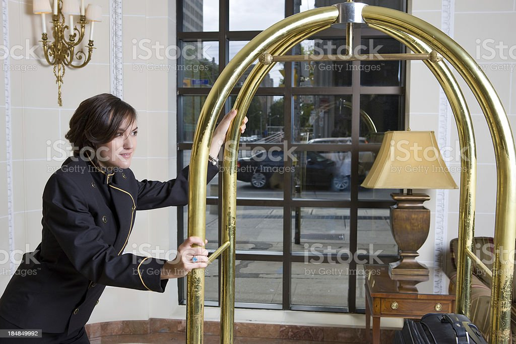 Bell Hop Pushing Luggage Cart In Luxury Hotel stock photo