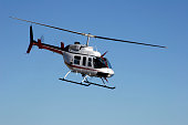A Bell Ranger helicopter flying on a clear day