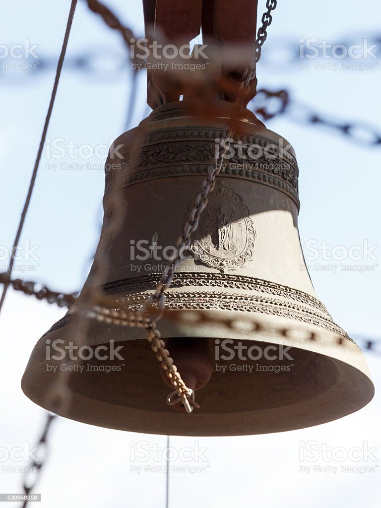 Bell surrounded by chains on the background of blue sky stock photo
