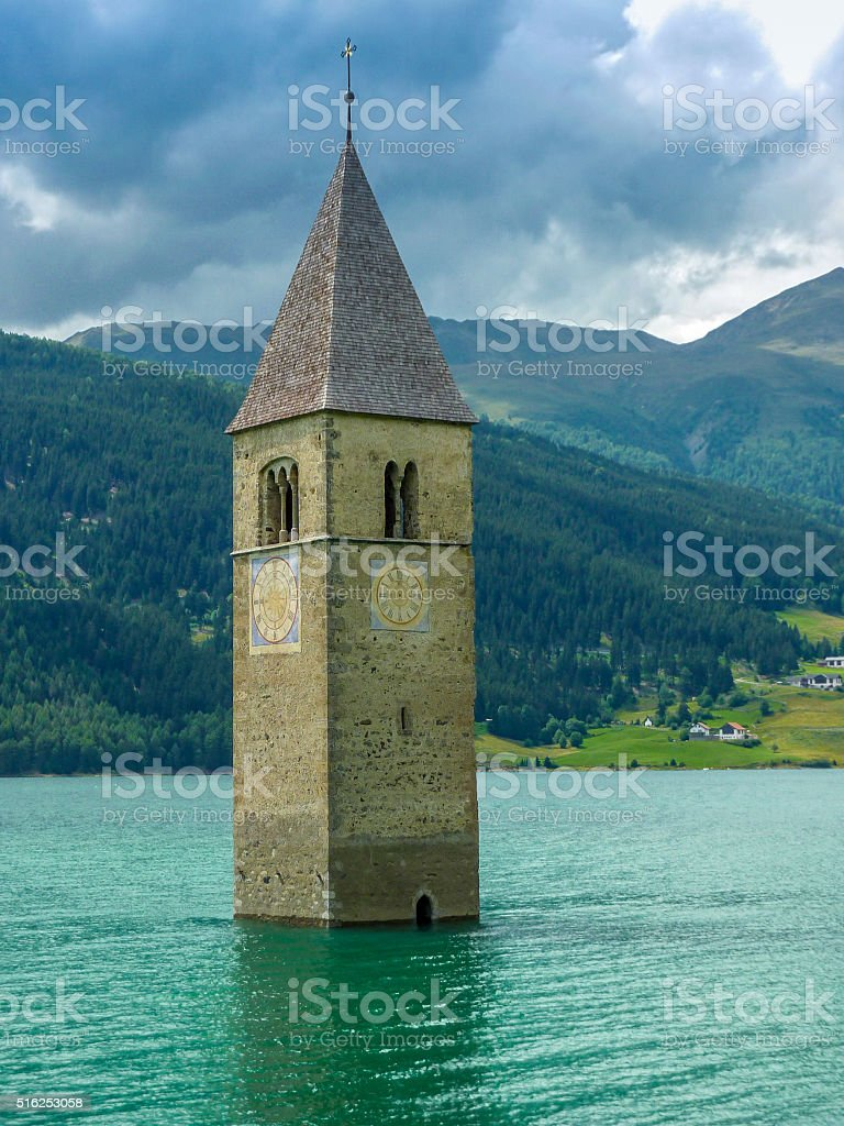 Bell tower of the Church in the Resia lake - 2 stock photo