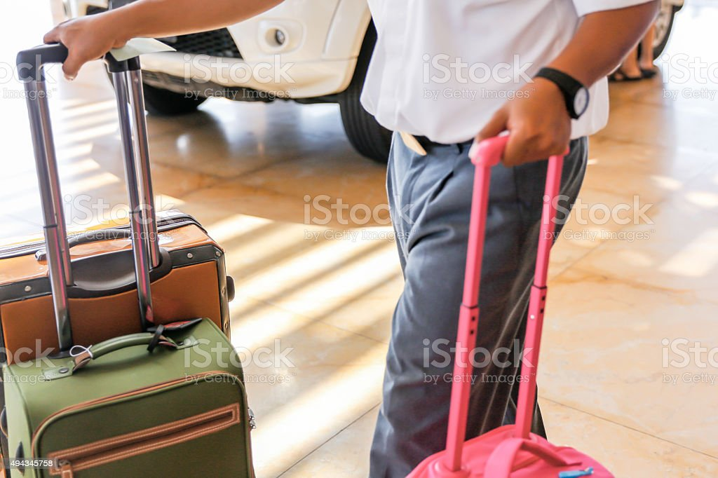 Bellboy carrying heavy luggage in drop off zone hotel entrance stock photo