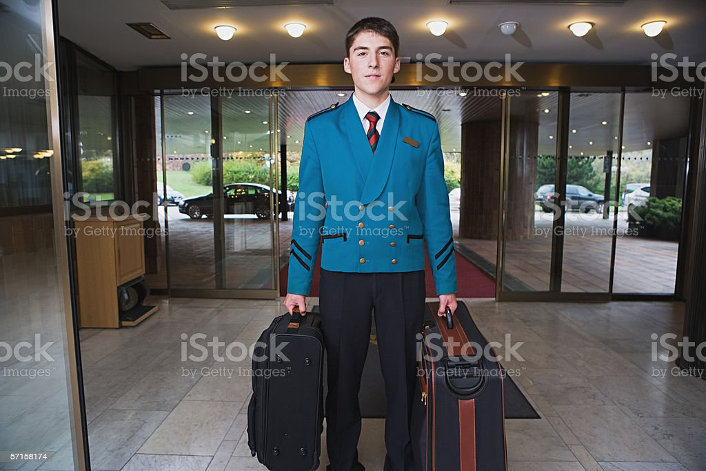 Bellboy carrying suitcases stock photo