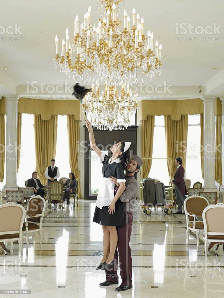 Bellboy holding up maid dusting chandelier in hotel foyer stock photo