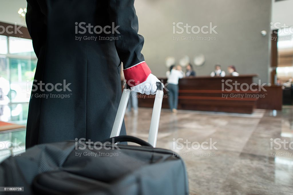 Bellboy pulling bag through the hotel stock photo