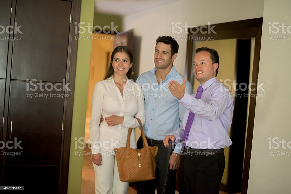 Bellboy showing room to a couple at the hotel stock photo