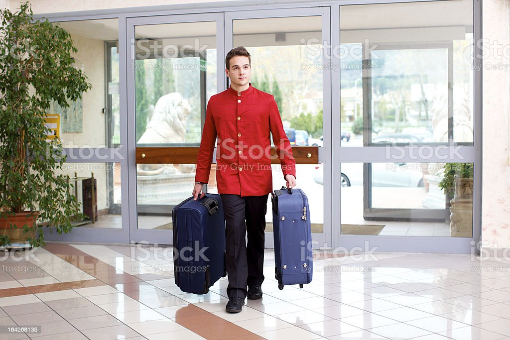 Bellhop carrying luggage stock photo