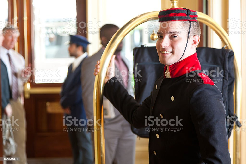 Bellhop holding luggage cart while waiting for hotel guests stock photo