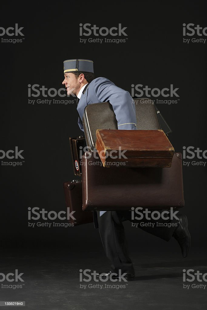 Bellhop running with suitcases stock photo