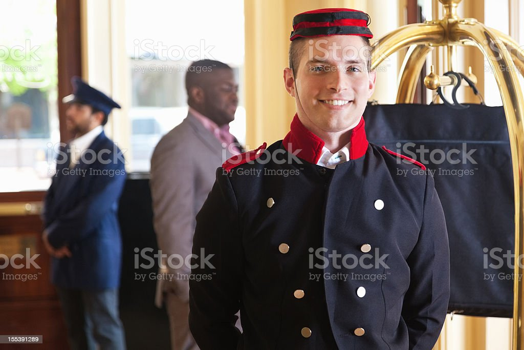 Bellhop standing in hotel lobby with guest's luggage on cart royalty-free stock photo