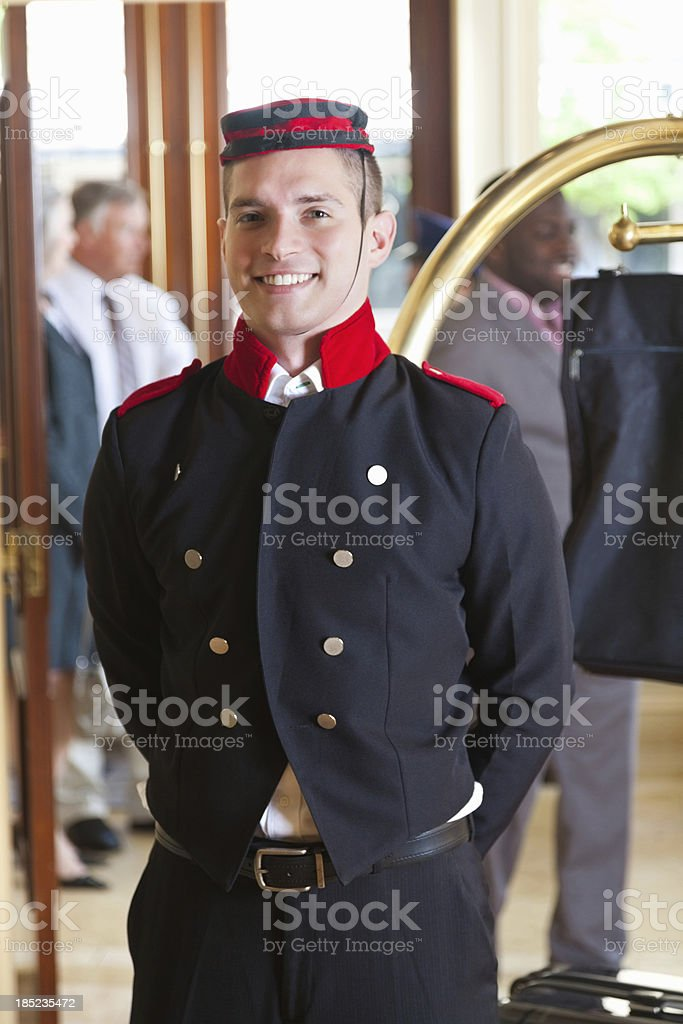 Bellhop standing with guest's luggage in a hotel lobby stock photo