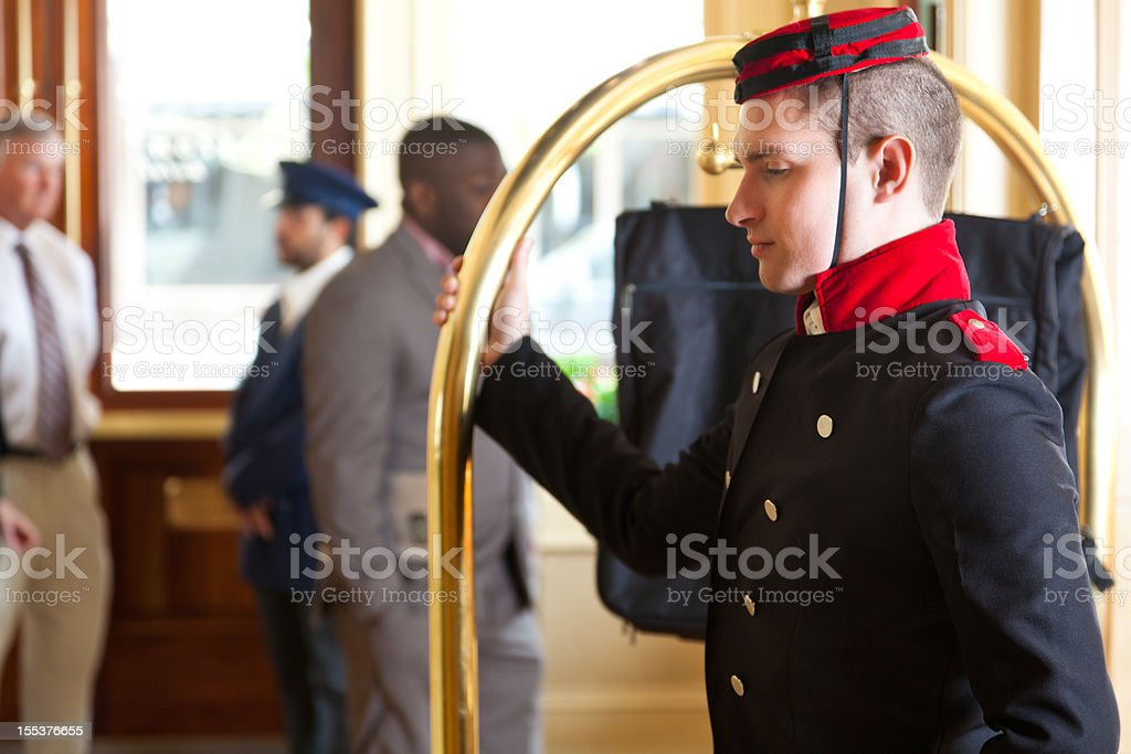 Bellhop with luggage cart waiting for hotel guest stock photo