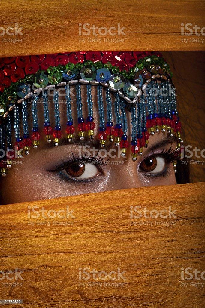 Belly dancer peeking from behind veil stock photo
