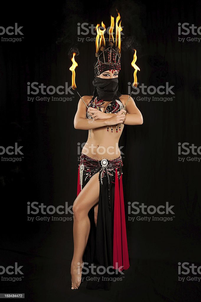 Belly Dancer wearing a hijab with fire headdress and torches royalty-free stock photo