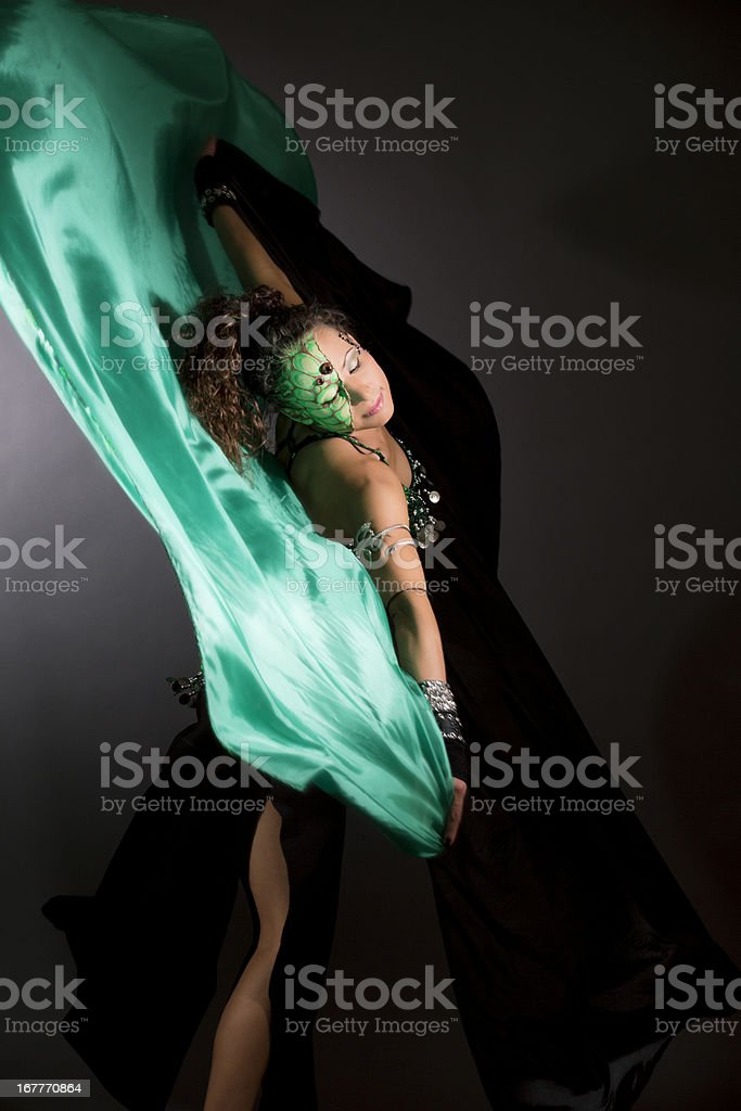 Belly dancer with stage makeup and silk scarves royalty-free stock photo