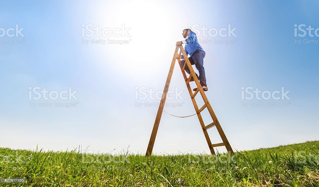 Below view of a businessman on ladder of success. stock photo