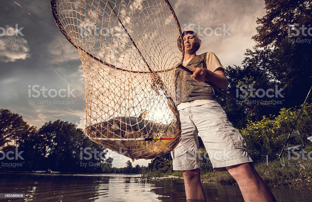 Below view of a fisherman holding his catch in net. stock photo