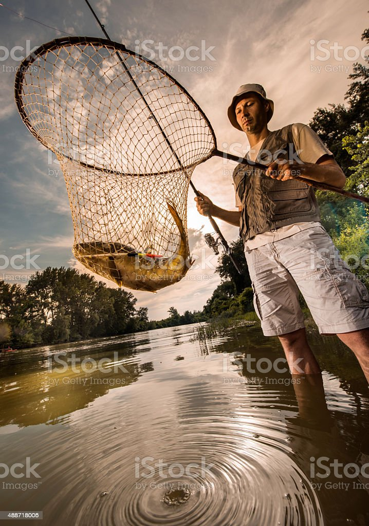 Below view of a fisherman holding his fish in net. stock photo