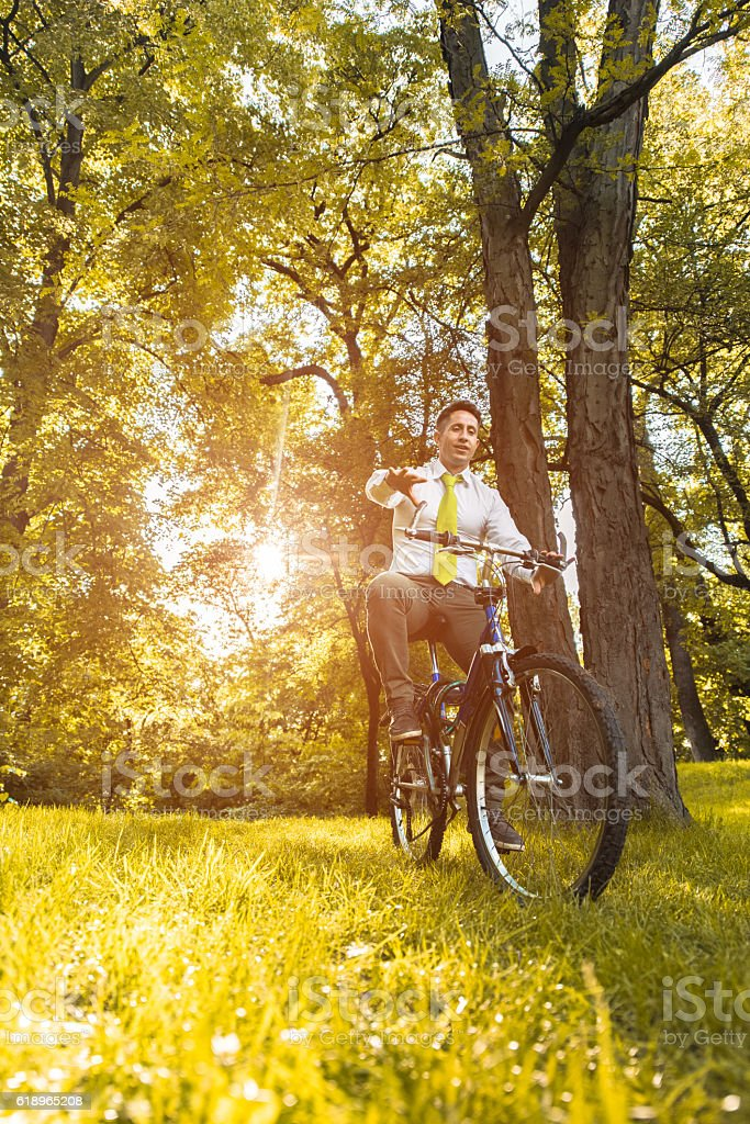 Below view of a happy businessman riding a bike. stock photo