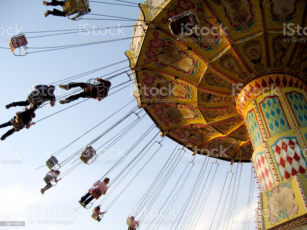 A below view of a large yellow Carousel that is mid spin royalty-free stock photo
