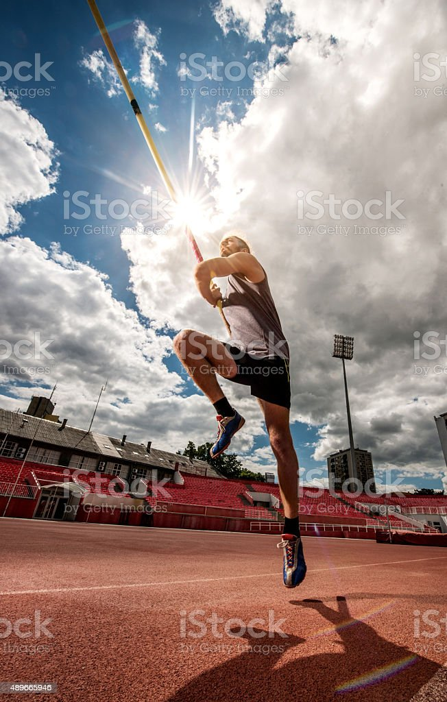 Below view of a man during a pole vault competition. stock photo