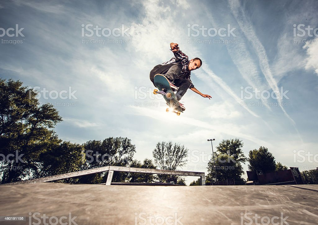 Below view of a street skateboarder in Ollie position. stock photo