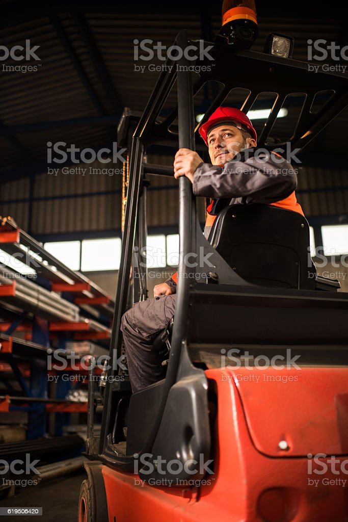 Below view of a worker driving forklift reversing. stock photo