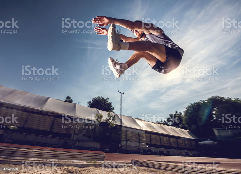 Below view of a young athlete in a long jump. stock photo