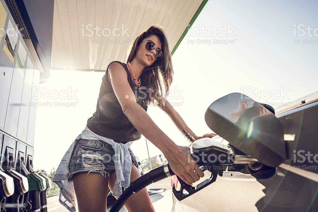 Below view of a young woman at gas station. stock photo