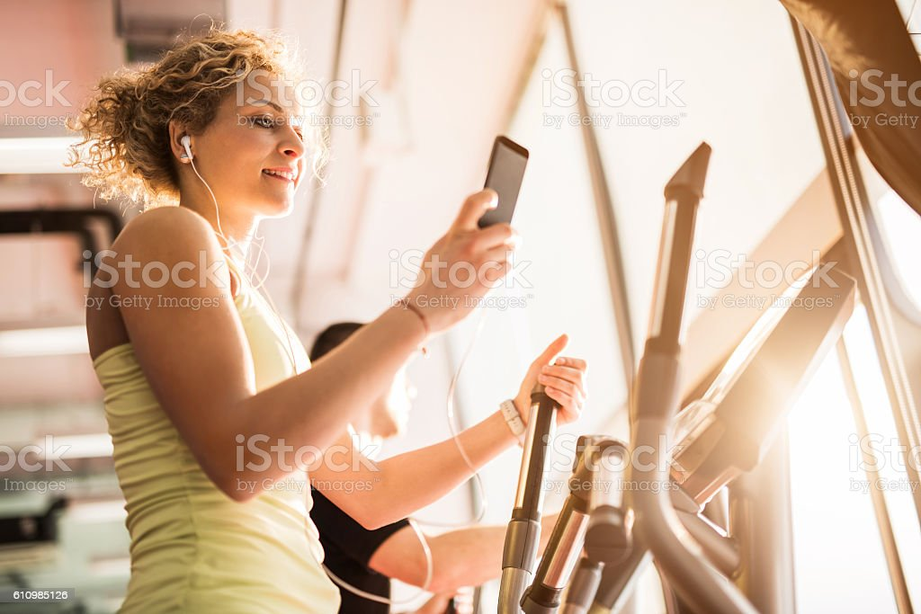 Below view of athletic woman listening music during exercises. stock photo
