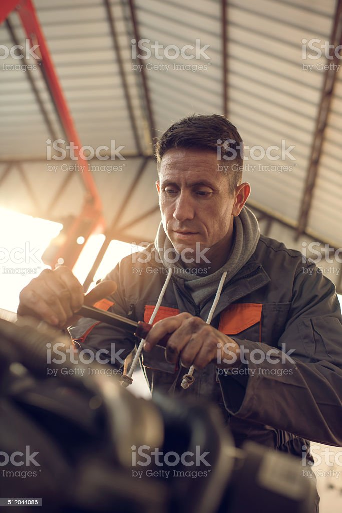 Below view of auto mechanic working in a repair shop. stock photo