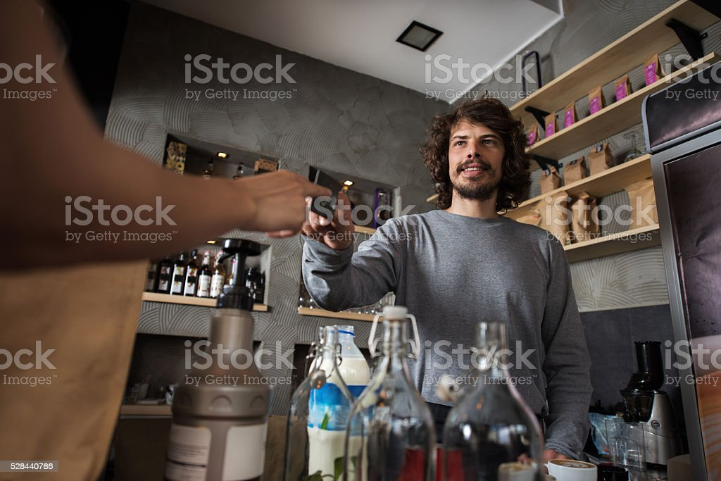 Below view of barista taking credit card from a customer. stock photo