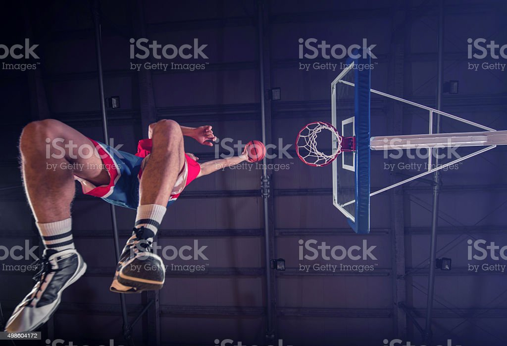 Below view of basketball player placing ball in the hoop. stock photo