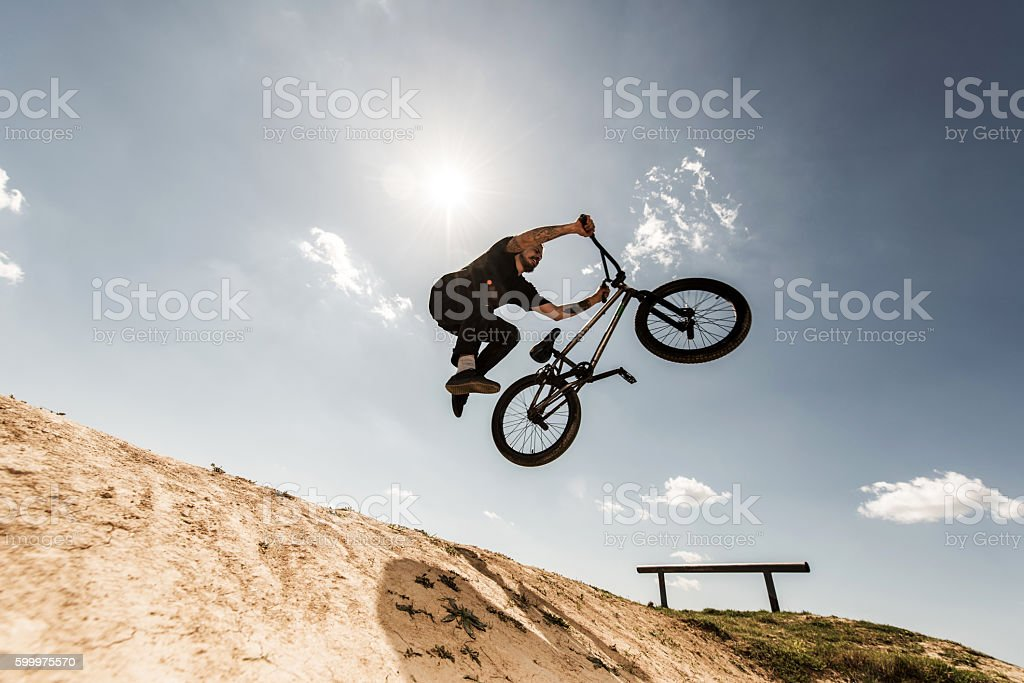 Below view of bmx cyclist jumping against the sky. stock photo