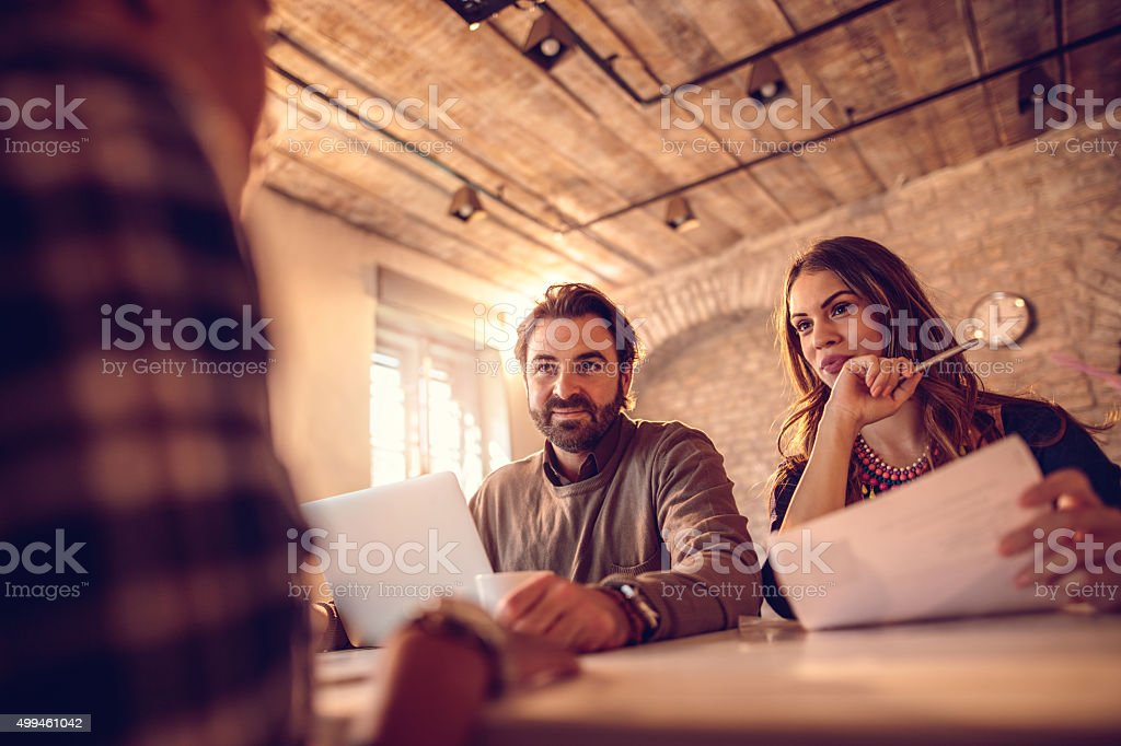 Below view of business people listening candidate at job interview. stock photo