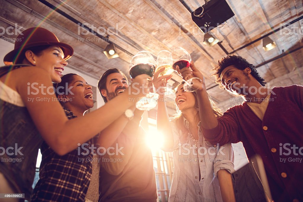 Below view of cheerful people having a toast. stock photo