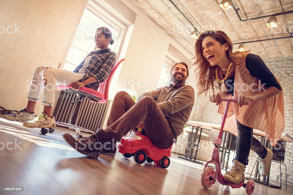 Low angle view of group of cheerful business friends having fun while...