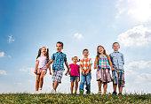 Below view of cute kids walking in a meadow.