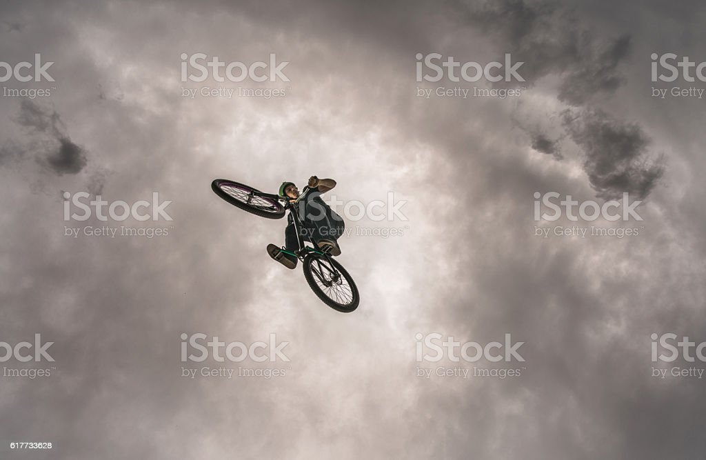 Below view of cyclist doing three sixty against the sky. stock photo