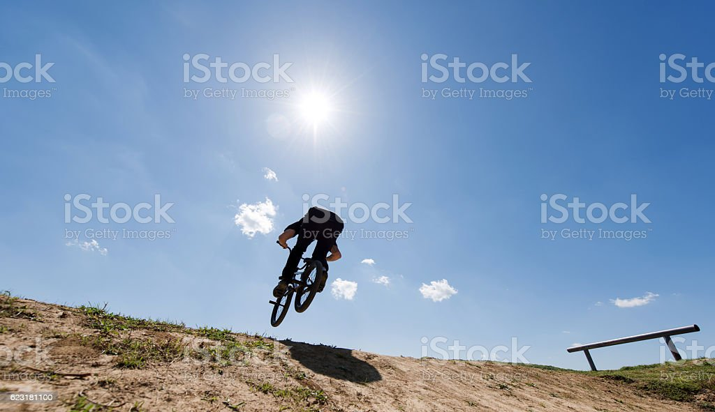 Below view of cyclist on dirt hill against the sky. stock photo