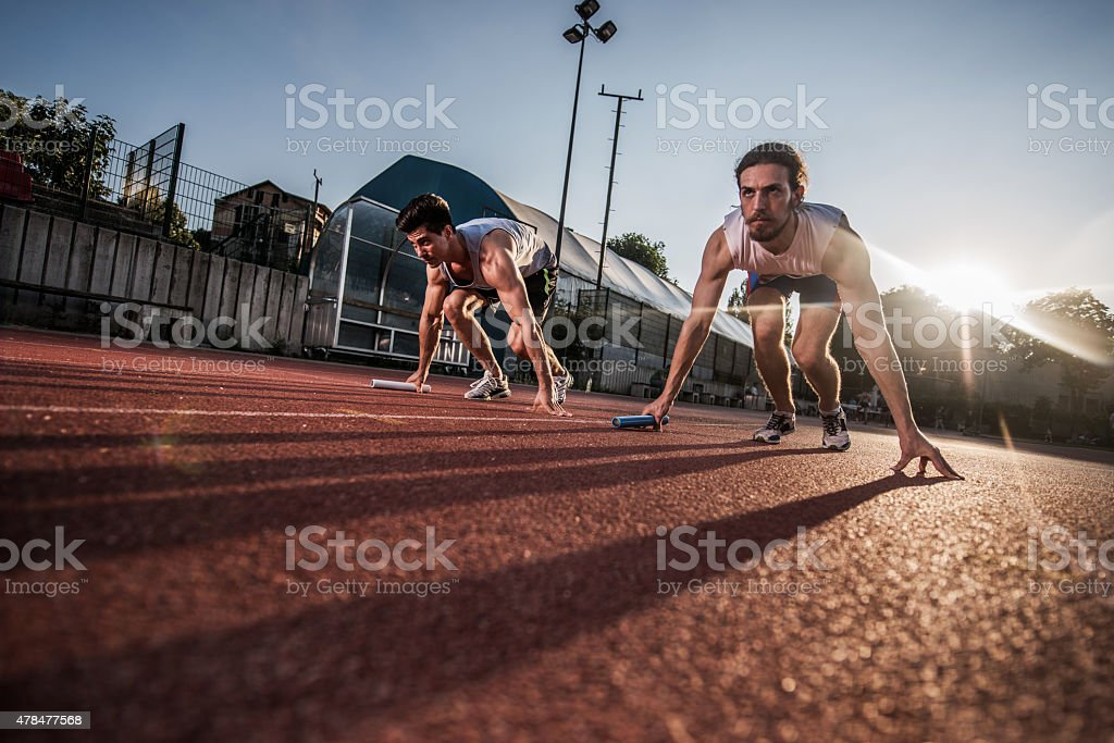 Below view of determined athletes ready to start relay race. stock photo