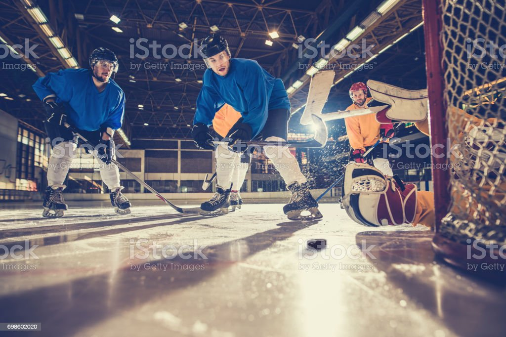 Below view of determined ice hockey players on a match in a rink. stock photo