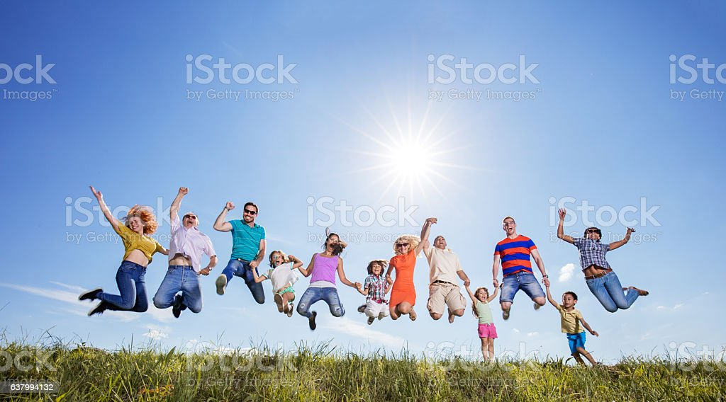 Low angle view of playful group of people jumping in a meadow and...