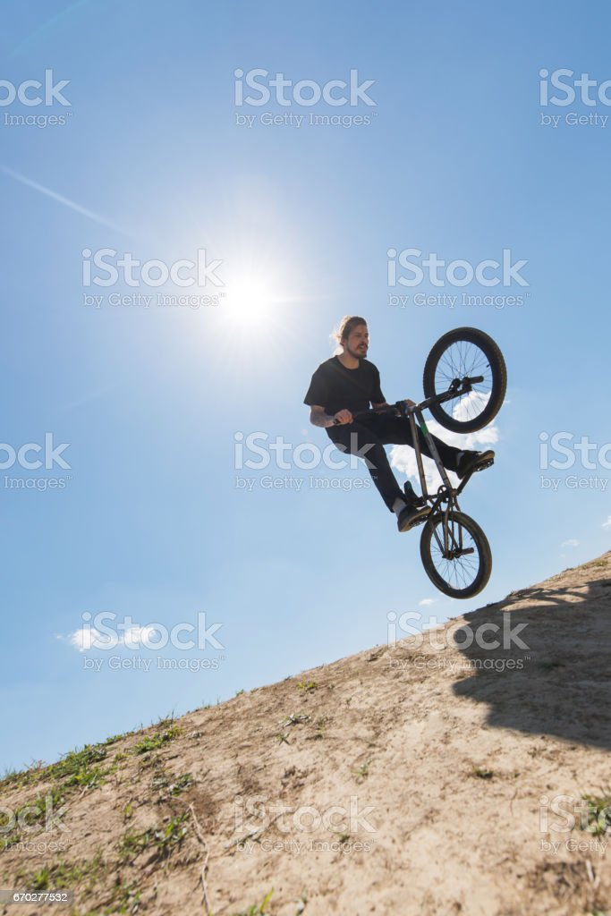 Below view of extreme cyclist against the sky. stock photo