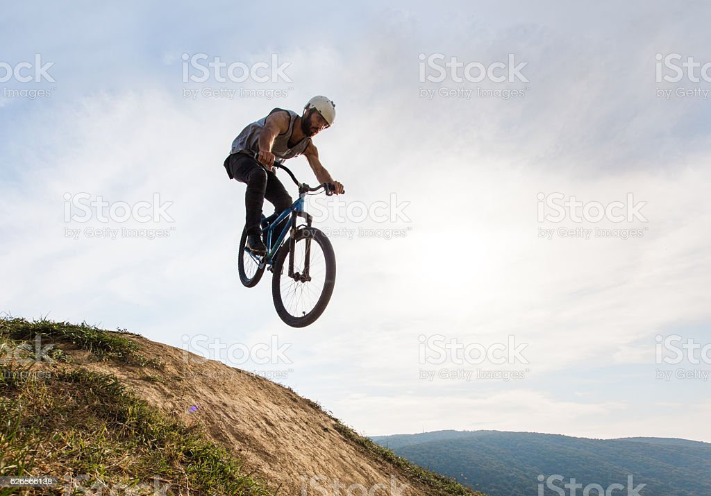 Below view of extreme cyclist doing straight air jump. stock photo