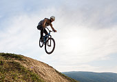 Below view of extreme cyclist doing straight air jump.