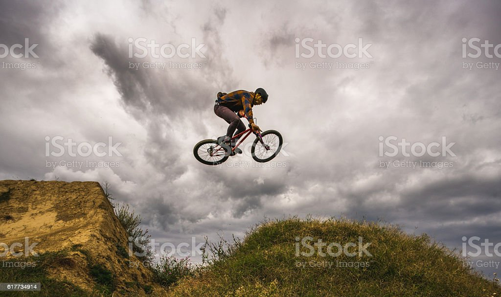 Below view of extreme cyclist doing tabletop against the sky. stock photo