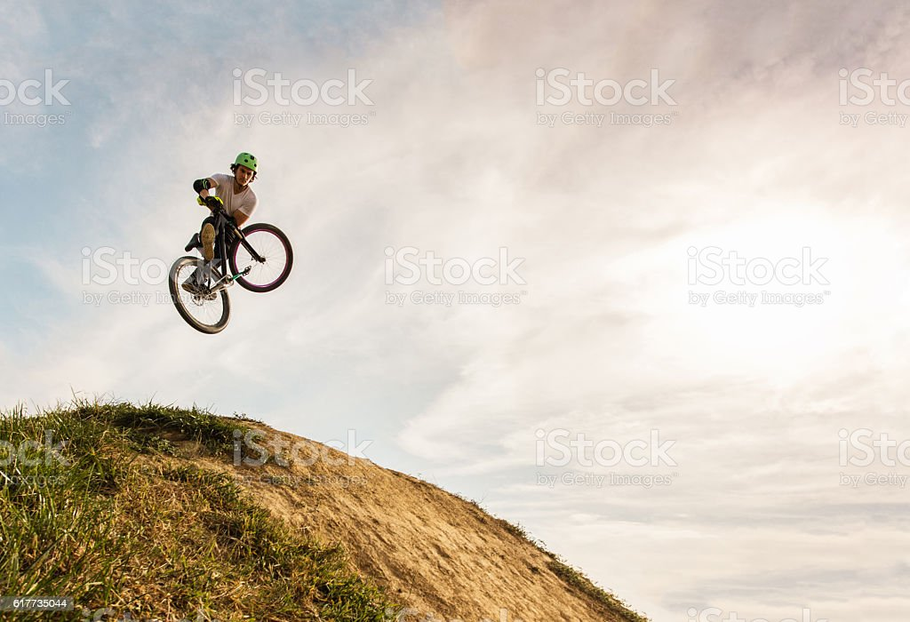 Below view of extreme cyclist performing invert move. stock photo
