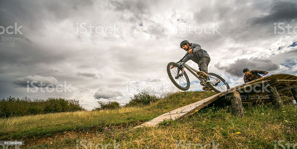 Below view of extreme cyclists riding fast over sports ramp. stock photo